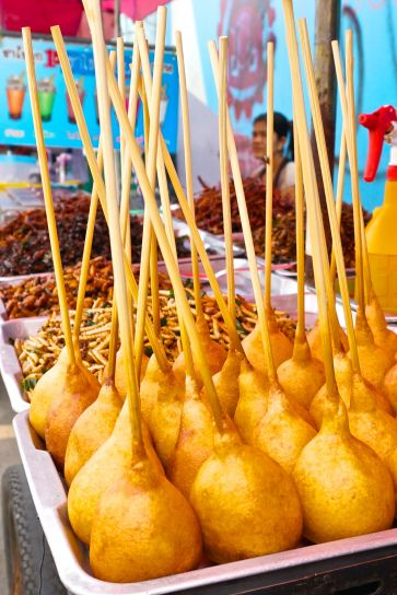 Pong Neng, the Thai version of a corn dog (sausage wrapped in pastry on a stick), one of the the best Thai street food dishes at Chatuchak Market JJ Market in Bangkok, Thailand.