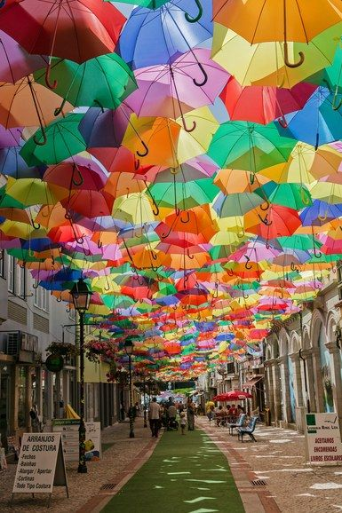Águeda's Umbrella Sky Project began in 2011 as a part of the Portuguese city's annual Ágitagueda Art Festival. Each summer, when temperatures soar, a handful of Águeda's narrow streets feature canopies of colorful umbrellas that provide shade to the pedestrians below | archdigest.com