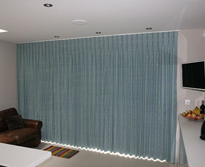 The Curtains Run Width Of Room On A White Powder Coated