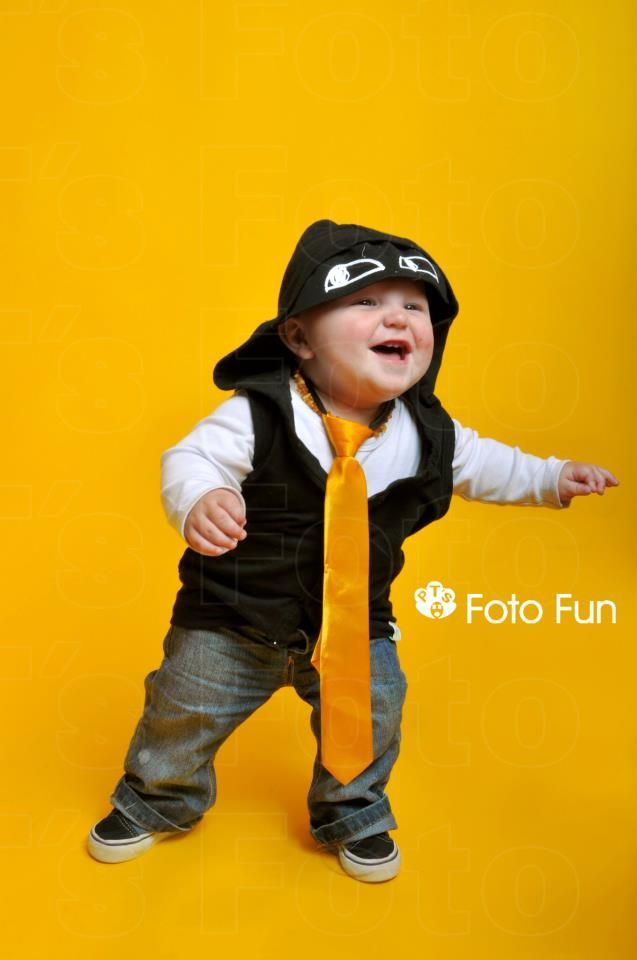 fun baby boy with trendy hood and yellow tie, first steps