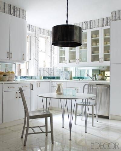 FASHION DESIGNER JACKIE ASTIER'S NYC KITCHEN INTERSPERSES THE WHITE CABINETRY AND CALACATTA MARBLE FLOORING WITH A SEPIA-TONED TREE-LINED WALLPAPER FROM COLE AND SON AND DARK DRUM PENDANT LIGHT.