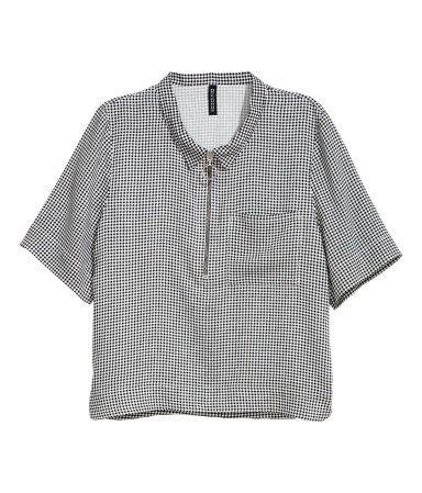 Svart/Vit rutig. En kort, vid skjorta i vävd viskos. Skjortan är kortärmad och har krage med dragkedja upptill. Slitsar i sidorna och något längre bakstycke