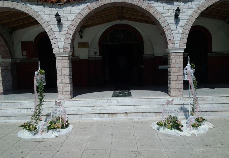 Στολισμός βάπτισης με κλουβιά στην είσοδο της εκκλησίας. Δύο συνθέσεις με πρωταγωνιστή 2 vintage κλουβιά στην είσοδο της εκκλησίας. Η σύνθεση συνοδεύεται από πράσινους κισσούς λευκές και ροζ κορδέλες από δαντέλα ενώ έχει τοποθετηθεί πάνω σε λευκά υφάσματα.