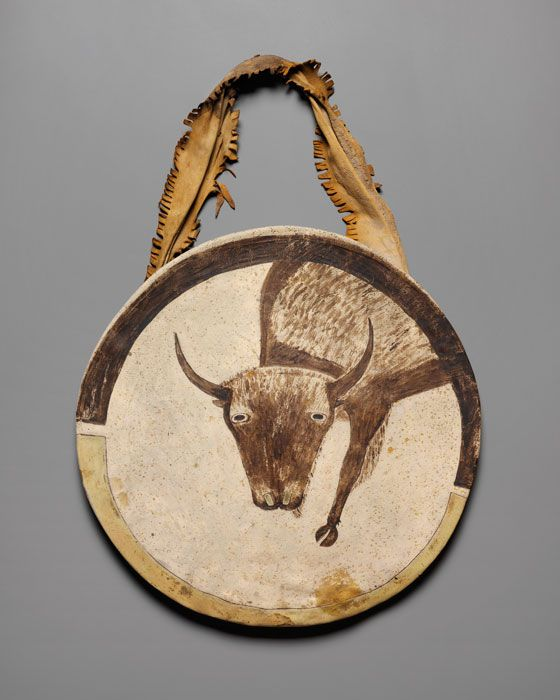"Shield, Arikara, North Dakota, ca. 1850. Buffalo rawhide, native leather, and native pigment, diameter: 20"", An 1850 shield, a masterpiece of Plains Indian visionary painting. This shield and cover (shown on front) from the Arikara is embellished with the image of a buffalo bull, the owner's guardian spirit, which would have been revealed to him in a vision during a prolonged period of fasting and prayer."