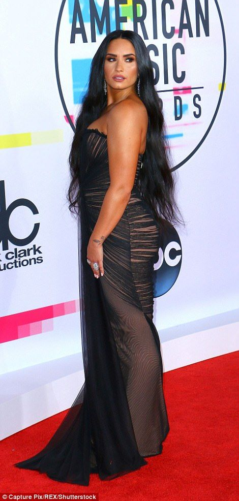 Sultry:Demi, 25, turned heads in her strapless lace gown; the singer flaunted her assets in the low-cut dress