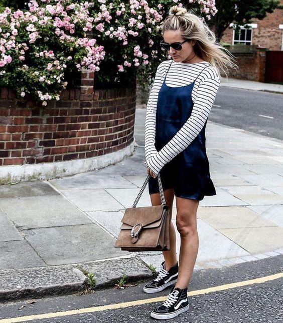 Look lindo e estiloso, com vestido azul de alcinhas em cima de blusa listrada de manga longa, bolsa e tênis