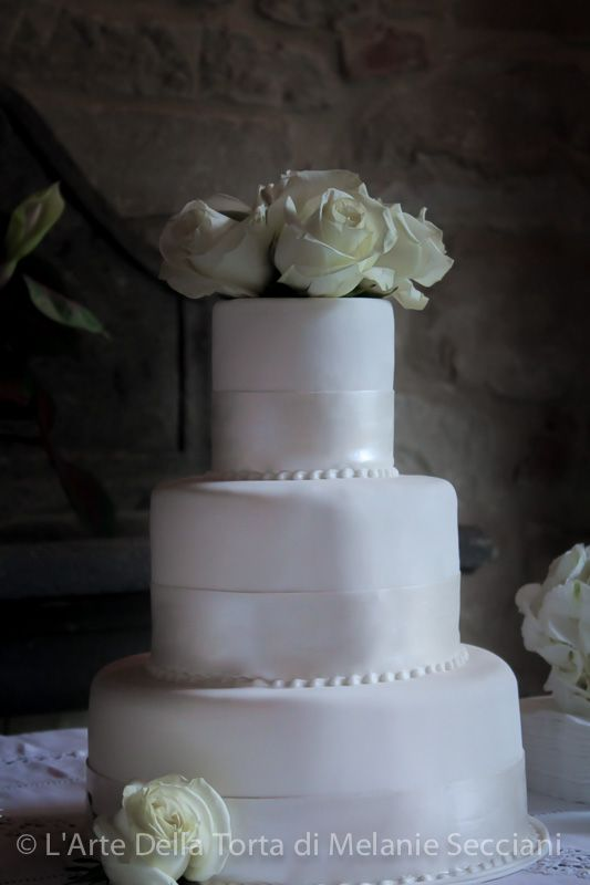 Tuscany Wedding cake by L'Arte Della Torta di Melanie Secciani in Florence, Italy. This Three tier all white wedding cake, created for a wedding at Villa Bel Poggio, in Reggello, Tuscany. Vanilla Cake with Madagascar Vanilla Mousse. The simple all white tiers were embellished, with pearlised sugar ribbon and fresh roses.  Thinking this white on white color scheme