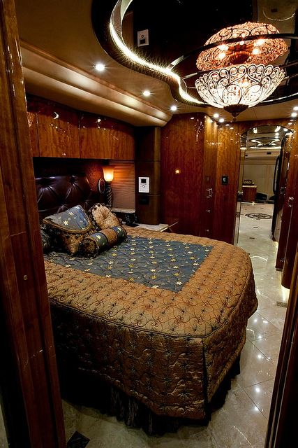 This Stateroom's gets its Regal look from the handcrafted dark wood cabinetry, Leather headboard, elegant bedding and classy chandelier.