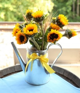watering can centerpiece with sunflowers.  use a red ribbon to match lady bug theme