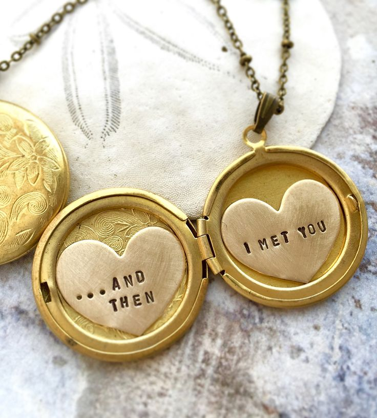 "A wearable memento of a special loved one, this dainty locket holds your memories close. The round locket holds two heart charms, stamped with with the sentiment, ""...And Then I Met You"". The antiqued silver or brass pendant is decorated in a floral motif and hangs on a dotted chain."