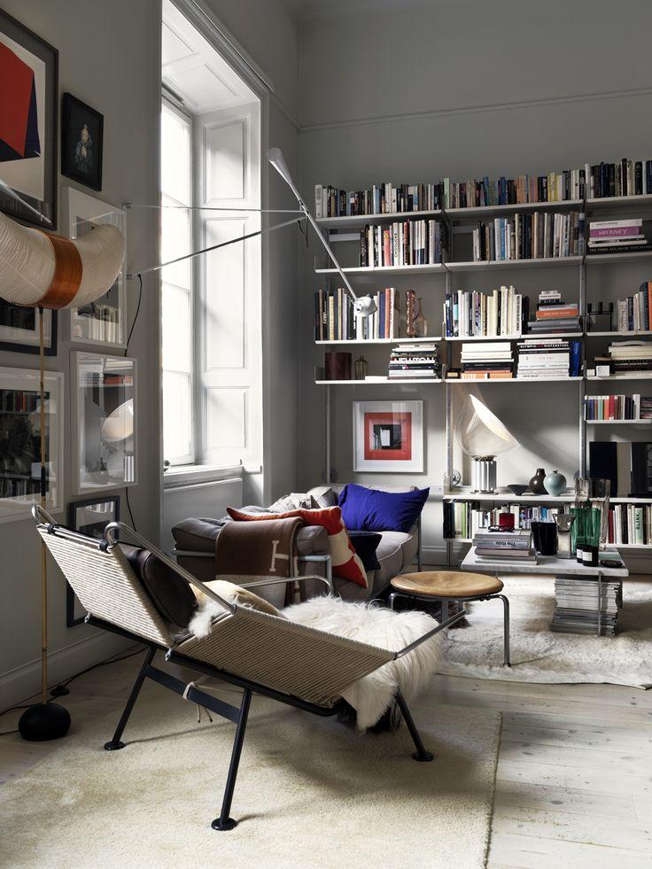 en bild på ett vardagsrum med bokhyllor och en fin fåtölj i förgrunden