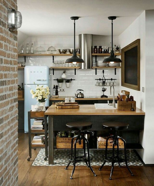 Industrial rustic kitchen with brick wall, iron hanging pendant lights, dark cabinets, butcher block counters