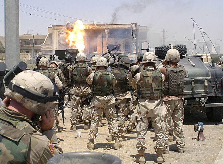 Soldiers of the 101st Airborne Division and U.S. Special Operations (Task Force 20) watch as a TOW missile strikes the side of a house occupied by Saddam Hussein's sons Uday and Qusay Hussein in Mosul, on 22 July 2003. Both sons were killed during the operation.
