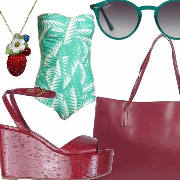 Costume intero con stampa floreale, zeppe color ciliegia allacciate alla caviglia, borsa shopper con manici lunghi in pelle, occhiali da sole con montatura verde, collana colorata