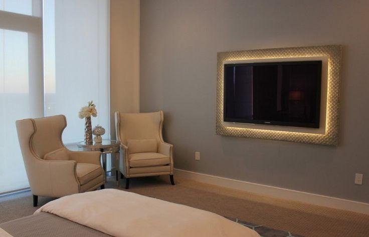 télé murale dans un cadre lumineux, mur gris et fauteuils beiges