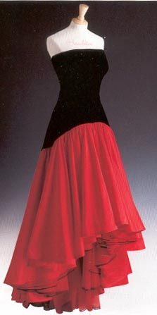 This striking gown made with a black velvet bodice and red taffeta skirt was designed by Murray Arbeid and worn by Diana at a London premiere in 1986. Also that year in September, she wore it to the America Cup ball. In 1987 she wore it in Spain where she added her own touch of one red, and one black long glove. This gown is lot #44 and it raised $ 25,300 for Diana's charities. It is owned by Suzanne King of Texas and is on long-term loan to Kensington Palace.