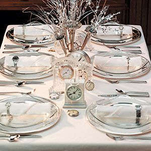 A collection of clocks and pocket watches set down the length of your table makes a spectacular showpiece on New Year's Eve. We used crystal and silver varieties to go with the glass dinner plates and silver chargers. (A quirky vase filled with silver metallic stars and streamers serves as a playful centerpiece.)