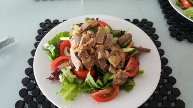 Steak with fat on a garden salad.