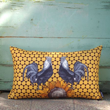 """October symphony"" A special pillow that combines brown geometric pattern background in sweet yellow-orange with two roosters in anthracite hue, who are dreaming lying under an orange sunflower. This pillow can be places independently on your chair or combined with pads of the same series in the lounge."