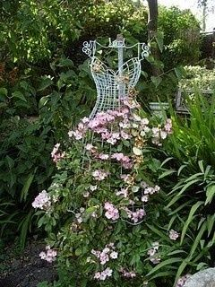 Thinking about using my metal dress form in my garden.  i love the way the flowers look for the skirt.....