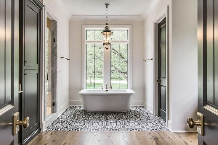 Black double doors open to a black and white Mediterranean bathroom features a lantern hanging over a freestanding tub fitted with a deck mount tub filler placed under windows atop a white, gray and black mosaic tiled floor flanked by a walk-in shower to the left and a water closet to the right.