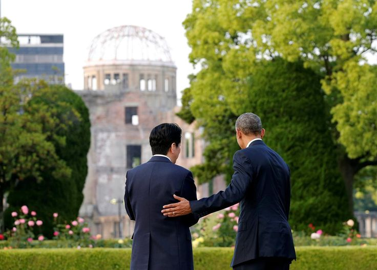 U.S. President Barack Obama (R) puts his arm around Japanese Prime Minister Shinzo Abe after they laid wreaths in front of a cenotaph with the atomic bomb dome is background at Hiroshima Peace Memorial Park in Hiroshima, Japan May 27
