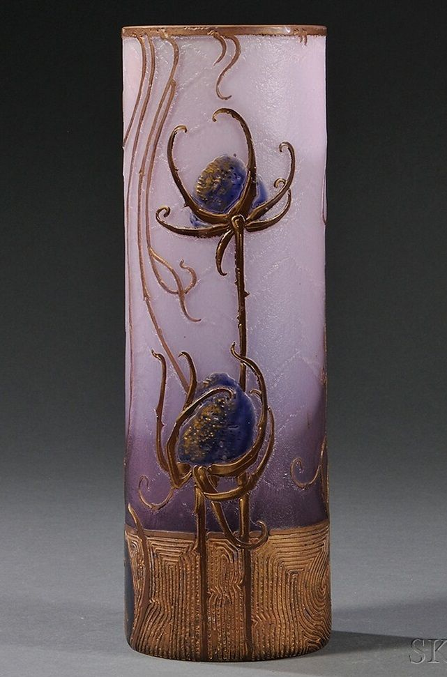 An Art Nouveau 1900. Of cylindrical form with enamelled decoration of stylised thistle flowers in gilt and purple enamel on amethyst glass