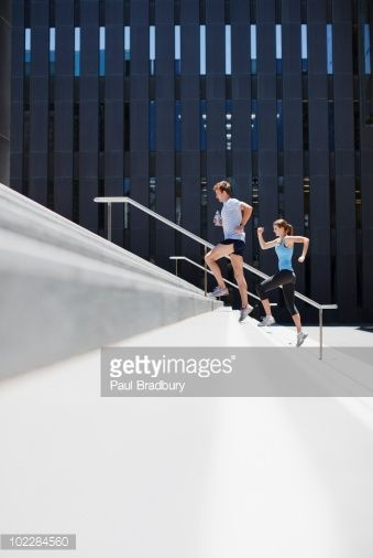 Couple running up urban staircase