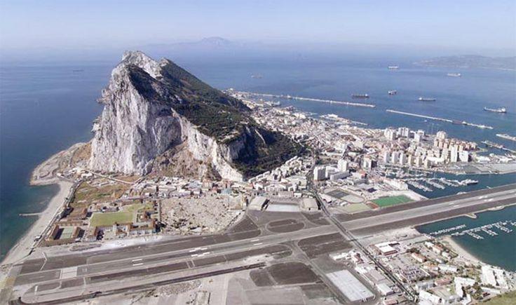 Gibraltar, território britânico encravado na Espanha, na entrada do Mediterrâneo: além de ficar justo ao lado do imenso rochedo de Gibraltar, sofre o efeito de ventos fortíssimos, é cercado de prédios altos e a pista, por falta de espaço, atravessa uma rodovia, com semáforo para os automóveis e tudo.  http://veja.abril.com.br/blog/ricardo-setti/tema-livre/assuste-se-com-o-video-os-10-aeroportos-mais-perigosos-do-mundo/