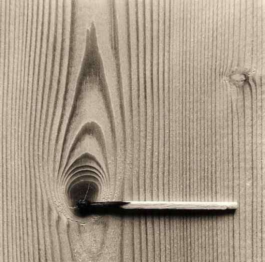 If the match was not in the center of the black spot on the wood the photo would not have the same feel.