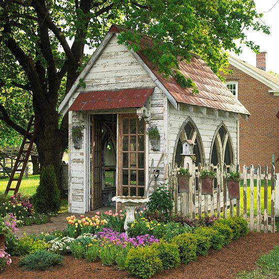 Gothic arched windows add to the antique feel of this garden shed. Stamped-metal roofing and hanging planters on the fence repeat the arched shape. A row of boxwoods brings order and definition to the entry garden.