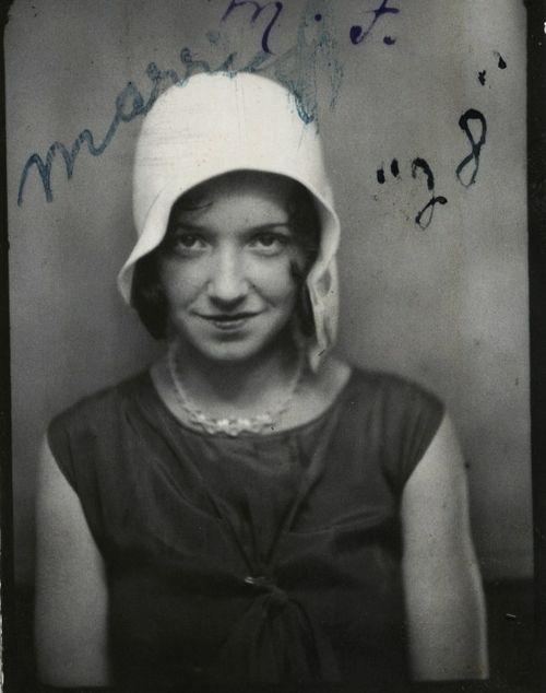 1928, vintage photo booth pic of young woman in a flapper hat.