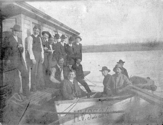 """Photograph shows men lined up at a dock with the Fraser River in the background. Writing on the back of the photo states: """"scow and fishing boat the Eighth Street slip"""" and also lists the following names: """"Fred Swanson (Fraser Hotel), Peter Paulson, Justus Swanson, Charles Erickson, Olaf Erickson."""" Ca. 1904.  IHP1078"""