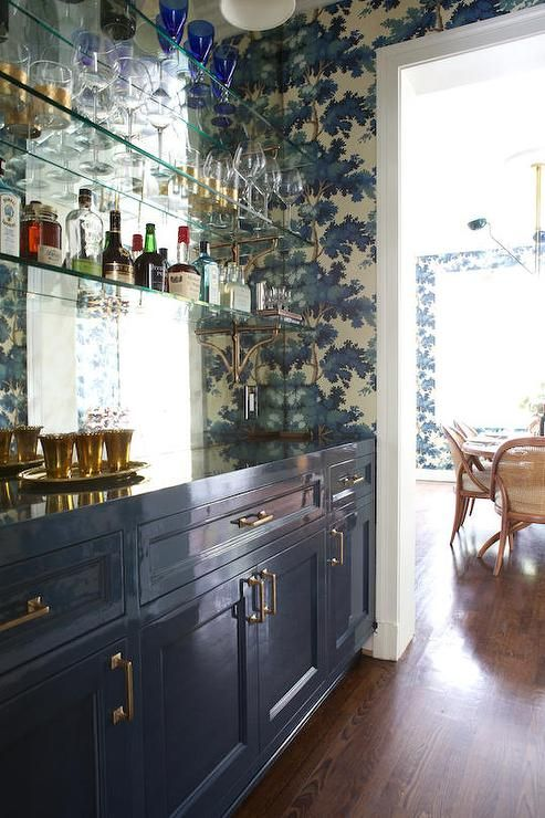 Amazing home bar features glossy blue lacquer cabinets adorned with brass pulls paired with blue ...