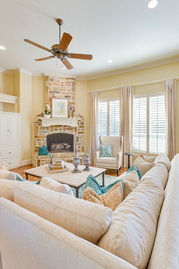 A brick fireplace, pale yellow walls, and bright blue accents give this bright and airy living room a contemporary style.