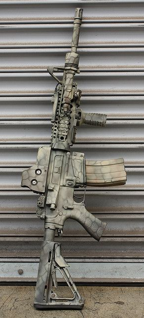 "theJanitor's AR-15/M4 clone, with excellent disruptive camouflage pattern. Unknown if he used Cerakote or not. From m4carbine.net forums. ""dark colors as the basecoat ( i used brown, olive, and the black of the original finish), and random applications of tan/khaki over a stencil. no special techniques, other than to try and break up the edges/lines of the rifle."" http://www.m4carbine.net/showthread.php?642-AR-Picture-Thread&p=424882#post424882"