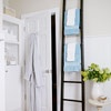 Tall ladder for towels make the room seem taller. Love the crown molding...
