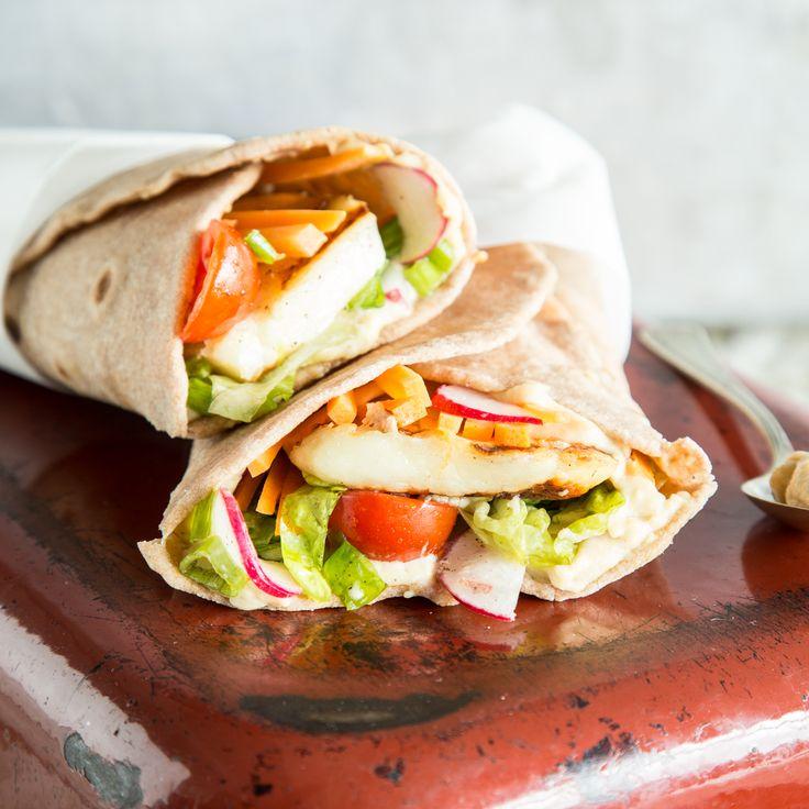 Gegrillter Halloumi wird auf bunten Salat gebettet und kann es sich mit cremigem Hummus in glutenfreier Buchweizentortilla eng eingerollt gemütlich machen.
