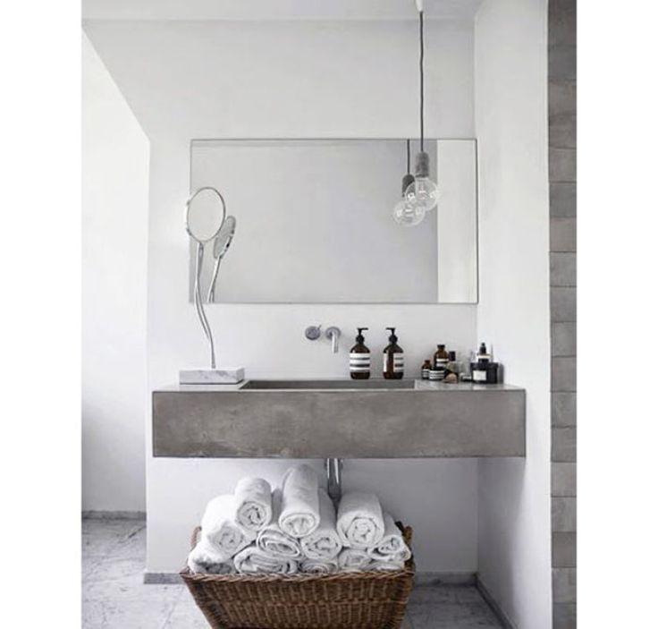 Para complementar o estilo minimalista, este banheiro optou por um cesto de vime abaixo da pia substituindo uma prateleira