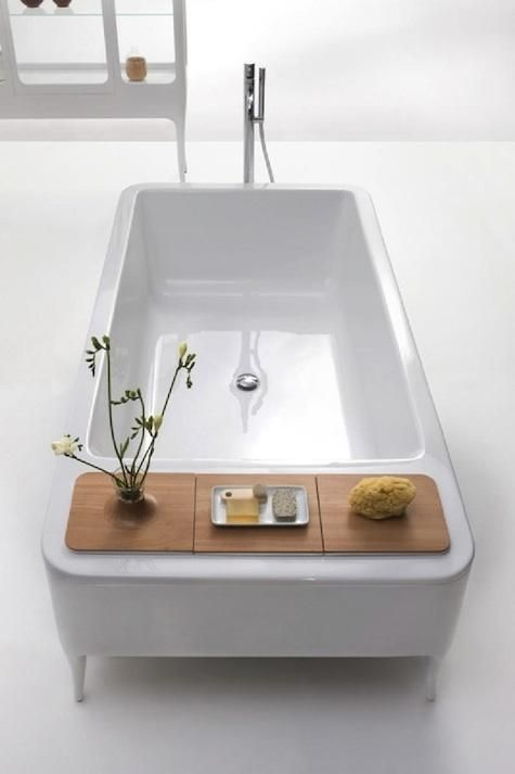 The white freestanding bath features built-in storage basins with beechwood covers.