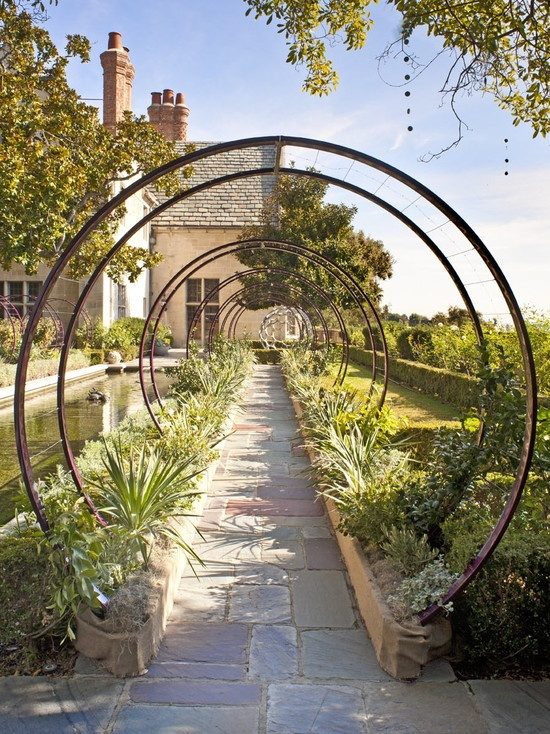 Lovely arches for a vine-covered tunnel pathway. Double-duty as they make picking the veggies much easier because they'll hang down towards the path.