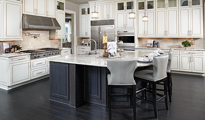 Highlights of this impressive Aldie, VA, kitchen include dark wood floors, contrasting white cabinets with glass inserts and a spacious center island | Harmon plan by Richmond American