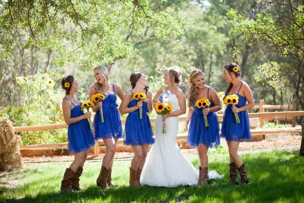 bride and bridesmaids, bridal party, cornflower blue bridesmaids dresses, cowboy boots, yellow sunflower bouquets, rustic blue and yellow wedding, Kim J Martin Photography