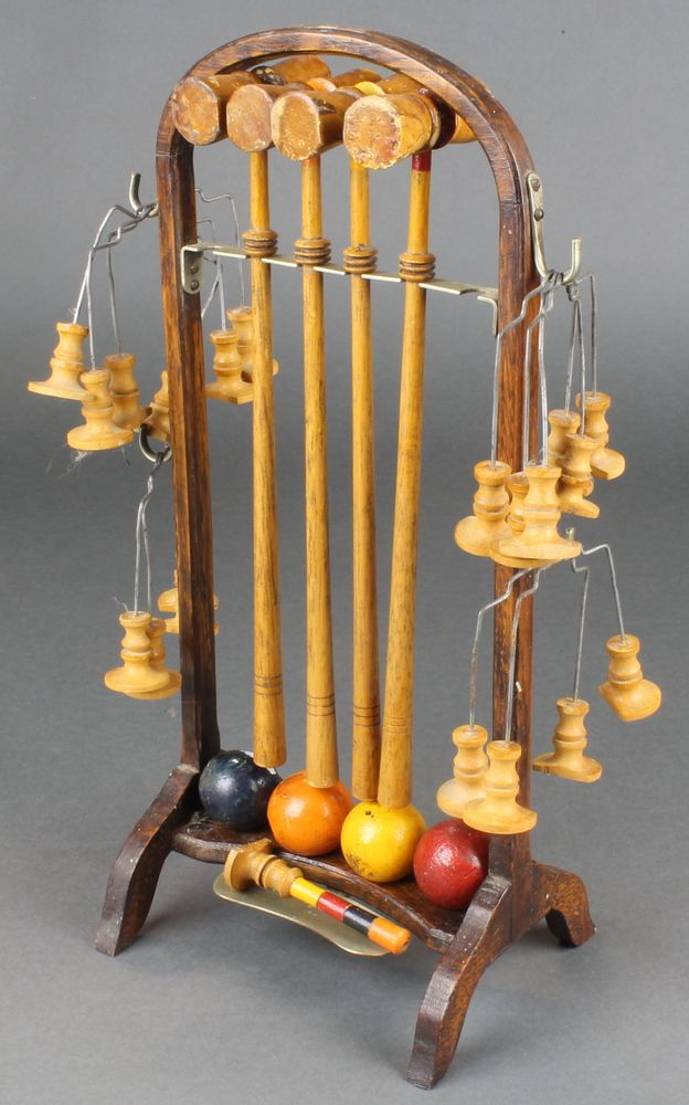 Lot 318, A table top croquet set comprising 4 turned mallets, 10 hoops, 4 coloured balls, stick marker (damaged), raised on a bent oak stand, est £50-100