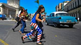 """Image copyright                  AFP                  Image caption                     La bandera estadounidense está presente por doquier en la Cuba actual, en un signo de los nuevos tiempos.   Ahora, cuando ya tiene más de 70 años, Elio García recuerda exactamente dónde estaba el 16 de abril de 1961. """"En la esquina de 23 y 12"""", dice, señalando la calle desde el portal de su casa en La Habana. """"Yo estaba hacia atrás en la multitud"""