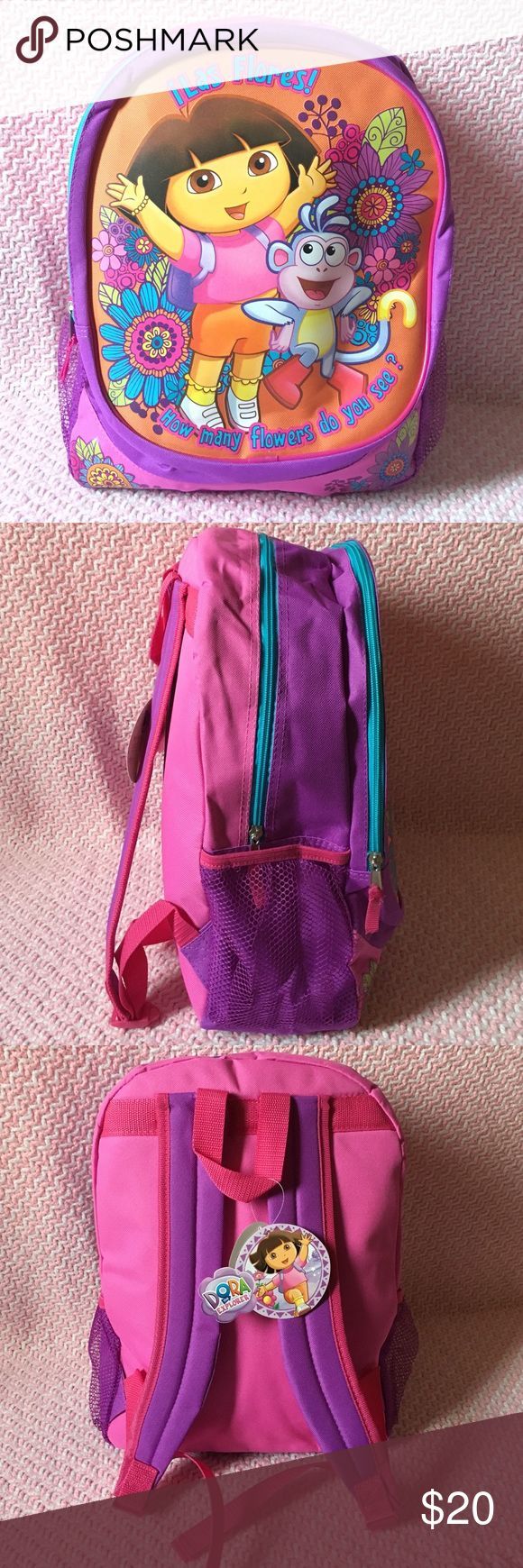 "Dora The Explorer Backpack NEW Dora backpacks, featuring Dora and Boots, says ""Las Flores"" ""How many flowers do you see?"", two compartment backpack, two holders for water bottles or cups, adjustable straps, multi color backpack. 16 inches long 6 inches wide Nickelodeon Accessories Bags"