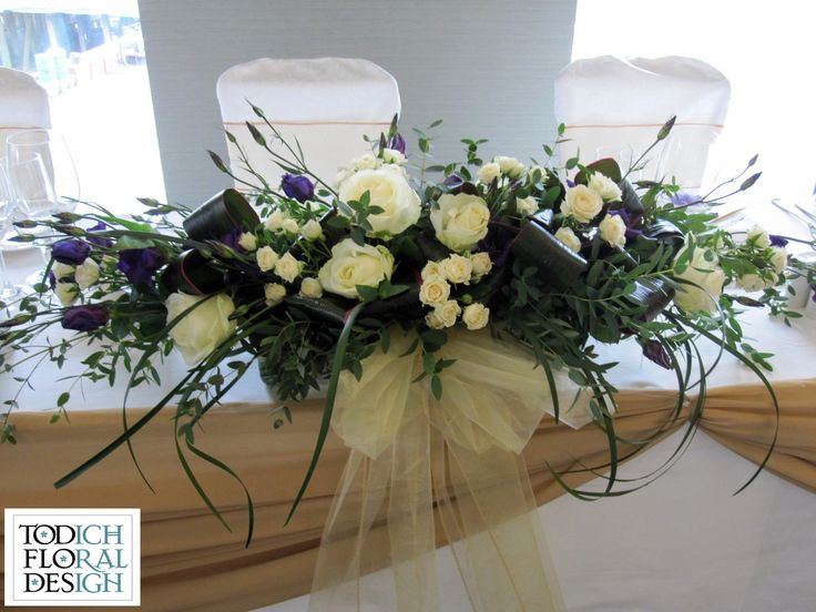 Top table arrangement into a long and low rectangular vase: Ivory roses, purple lisianthus, finished off with looped lily grass, cream pearls and ivory satin ribbon.