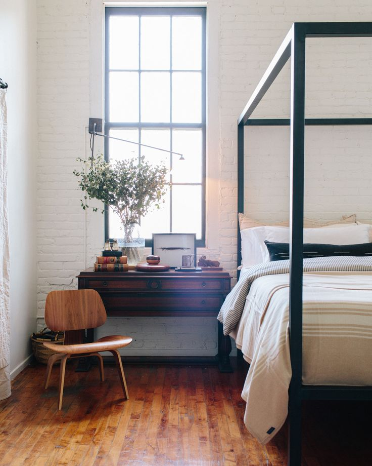 Bohemian Eclectic Midcentury Rustic Bedroom: A metal canopy bed, side table, and midcentury chair.