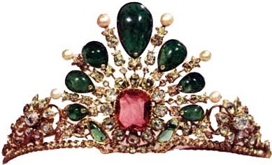 Emerald and Diamond Tiara: Its basic design is of a sunburst, with a 25 ct. pink spinel in the center. Each ray ends in a diamond blossom with a single pearl or emerald. The emeralds have holes in them which are covered with small diamonds. The holes suggest that the emeralds were previously used in other pieces. The largest emerald is 20 cts.