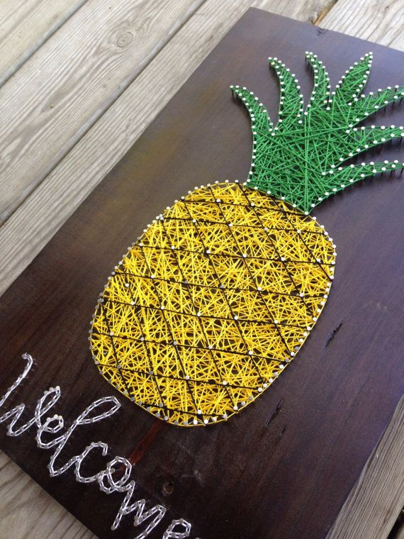 Pineapple Welcome String Art  Colors: yellow, green, black, white Wood Color: Golden Pecan  If you want to bring a bit of the tropics into your home, theres no better way to do it than with this Pineapple Welcome string art! You and your guests will see it each time they enter your home and immediately feel welcome. The plank is salvaged wood from a cedar tree that is sanded and cut to size. The wood had had a golden pecan stain applied and a thin, protective clear coat added on top. Nails…